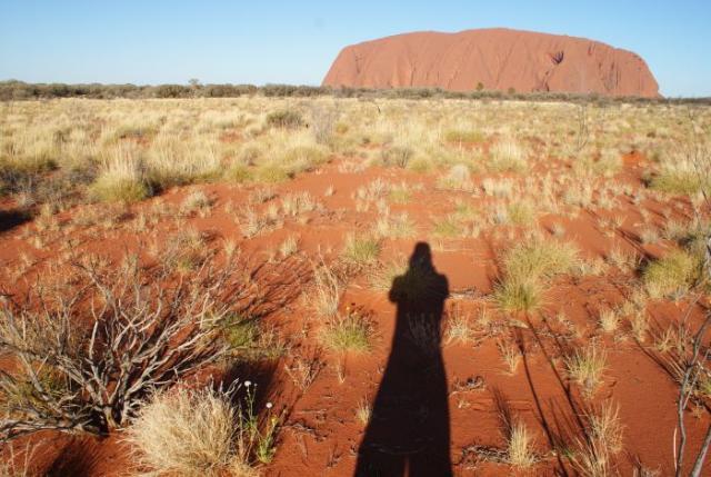 Osamocený dlouhý stín před posvátným Uluru - Centrální Austrálie
